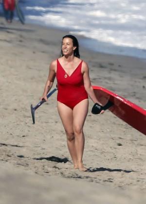 Alanis Morissette paddleboarding in red swimsuit -04