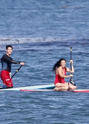 Alanis Morissette paddleboarding in red swimsuit -07
