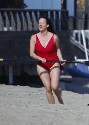 Alanis Morissette paddleboarding in red swimsuit -21