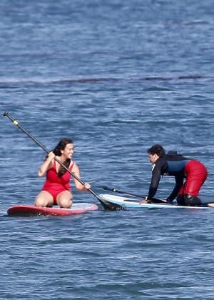 Alanis Morissette paddleboarding in red swimsuit -29