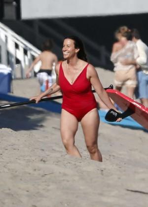 Alanis Morissette paddleboarding in red swimsuit -31