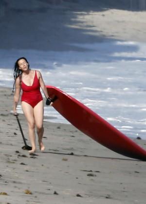 Alanis Morissette paddleboarding in red swimsuit -36