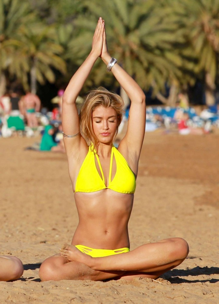 Amy Willerton in a yellow bikini doing yoga on the beach