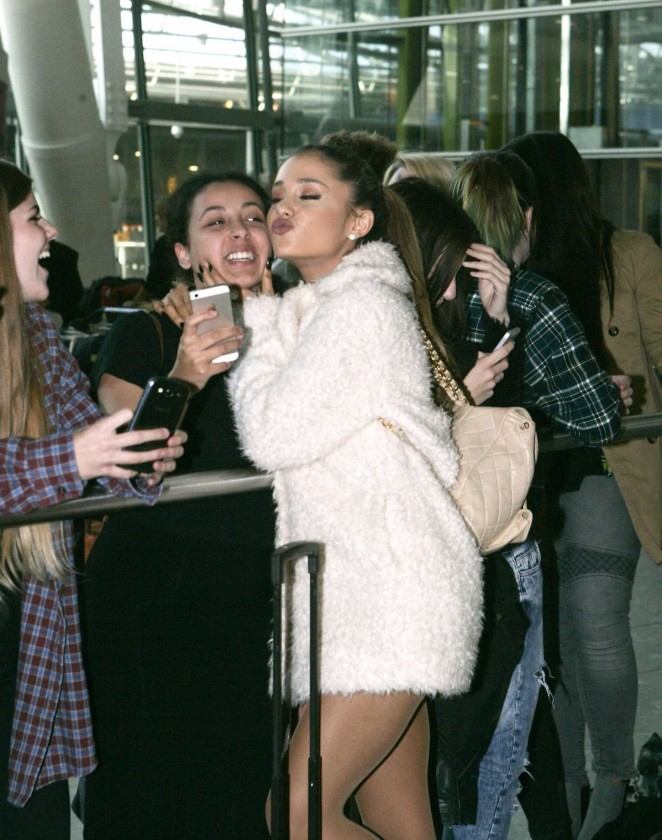 Ariana Grande Shows Legs in a fur coat at Heathrow Airport in London
