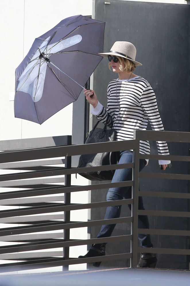 Jennifer Lawrence in Jeans and Umbrella Leaving an office building in LA