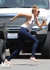 Miley Cyrus Running in a Jeans and White open top shirt in Toluca Lake