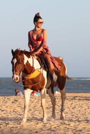 Alessandra Ambrosio - In a bikini horseback riding on the beach in Trancoso