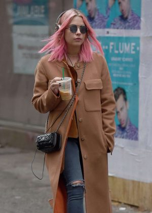 Ashley Benson in a beige coat while listening to music in New York