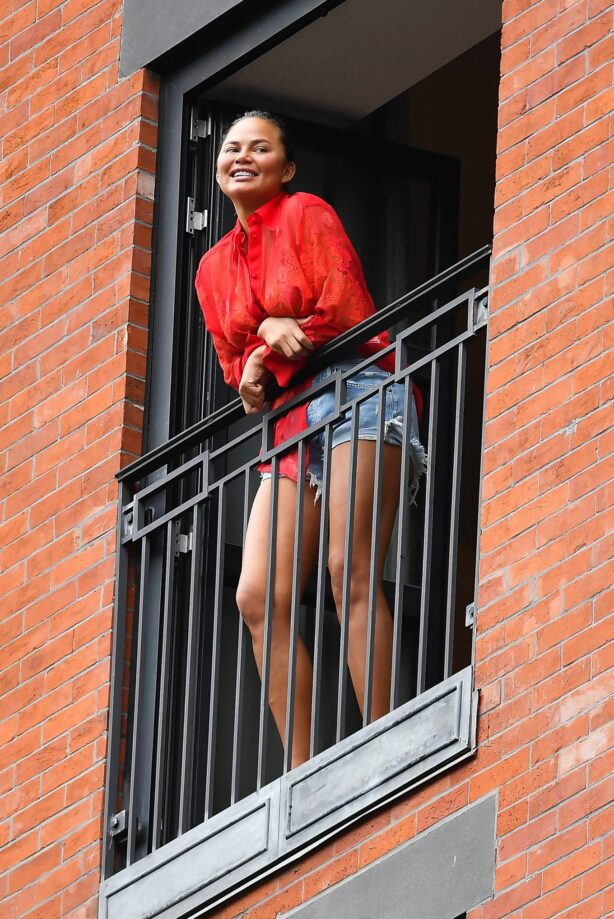 Chrissy Teigen - Wears a red top and jean shorts in Soho