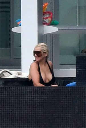 Christina Aguilera - Wears a black swimsuit in Miami