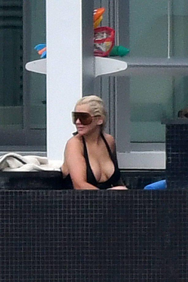 Christina Aguilera - Wears a black swimsuit in Miami