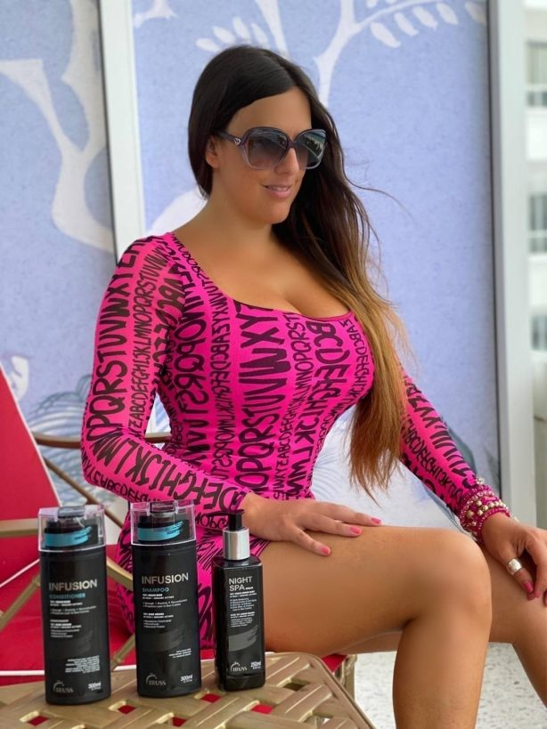 Claudia Romani - Wearing a neon pink dress and high heels on the balcony in Miami