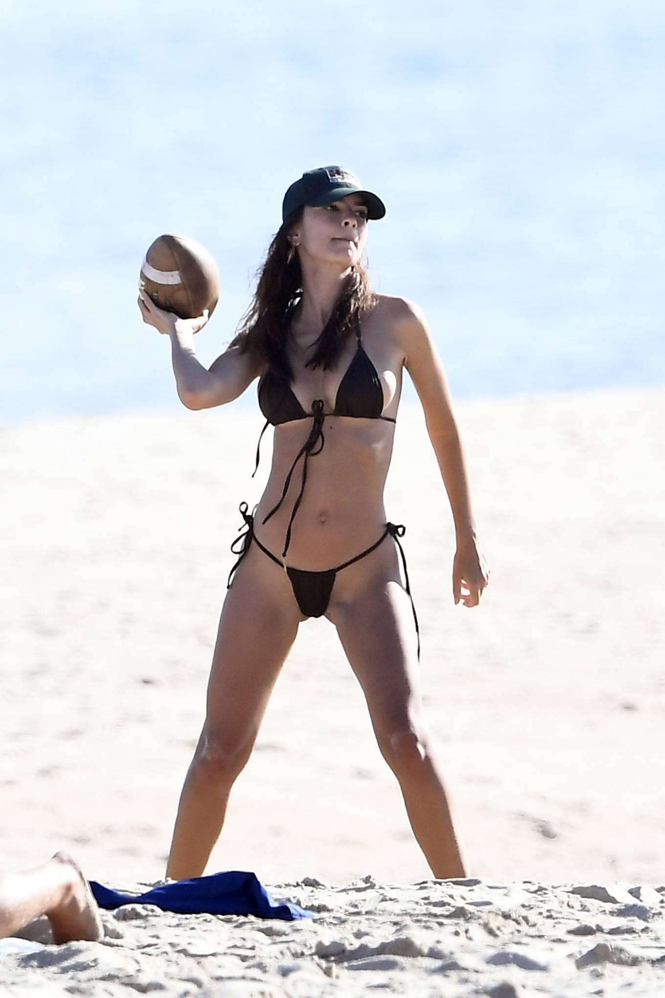 Emily Ratajkowski - In a black bikini playing football at the beach in East Hampton Hamptons