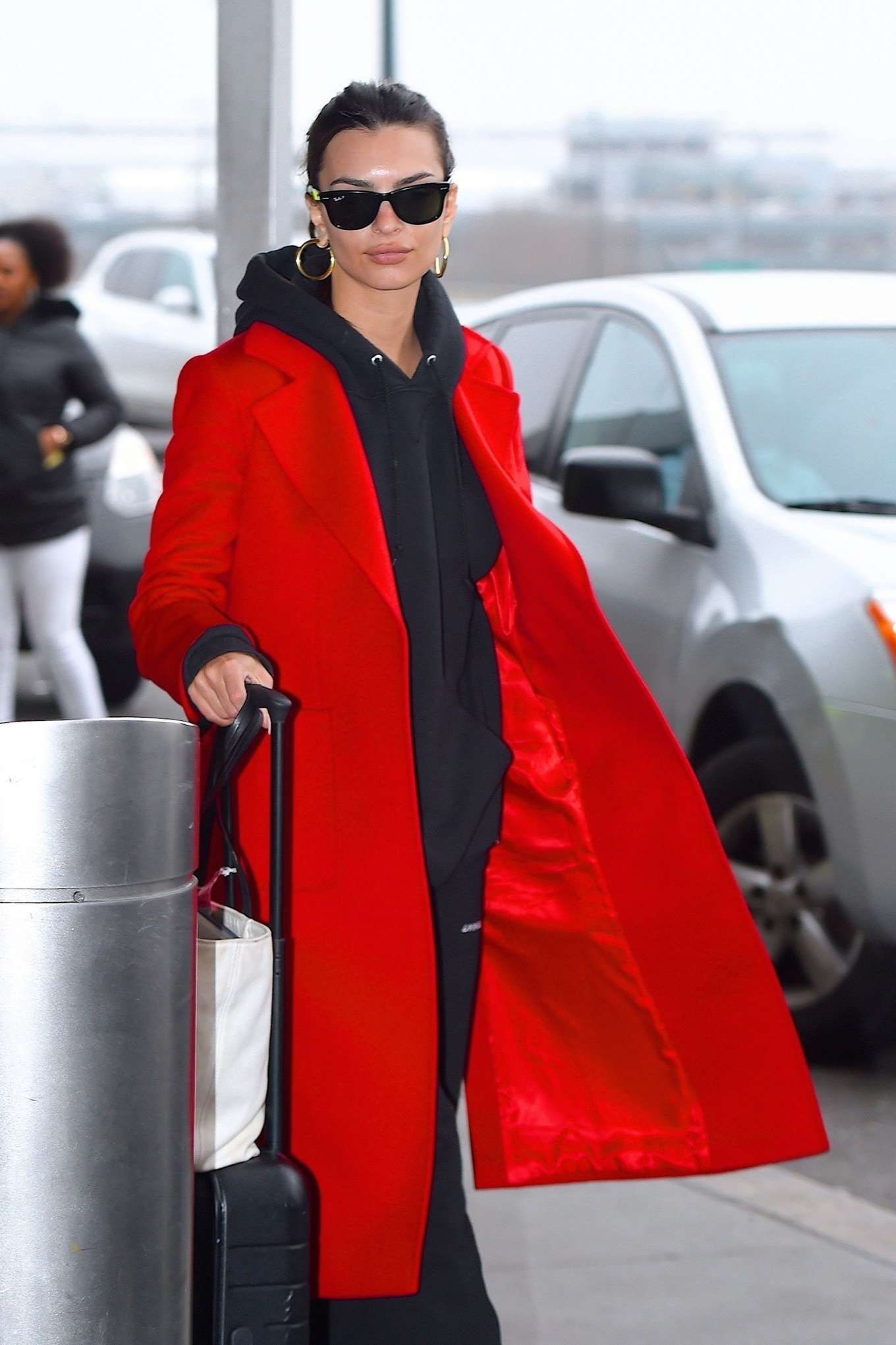 Emily Ratajkowski in red coat ready for flight at JFK airport