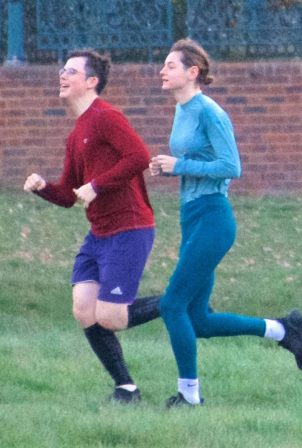 Emma Corrin - Jogging candids at a park with a mystery male friend in London