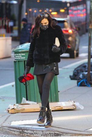 Famke Janssen - Wearing a Black Faux Fur Puffer Jacket with a mini-skirt in Manhattan