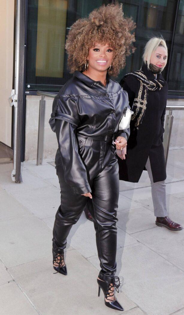 Fleur East - Wearing a leather one piece black jumpsuit in London
