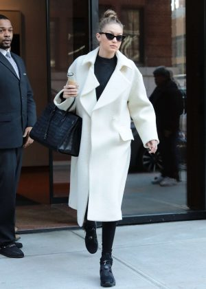Gigi Hadid in white coat leaving her home in NYC