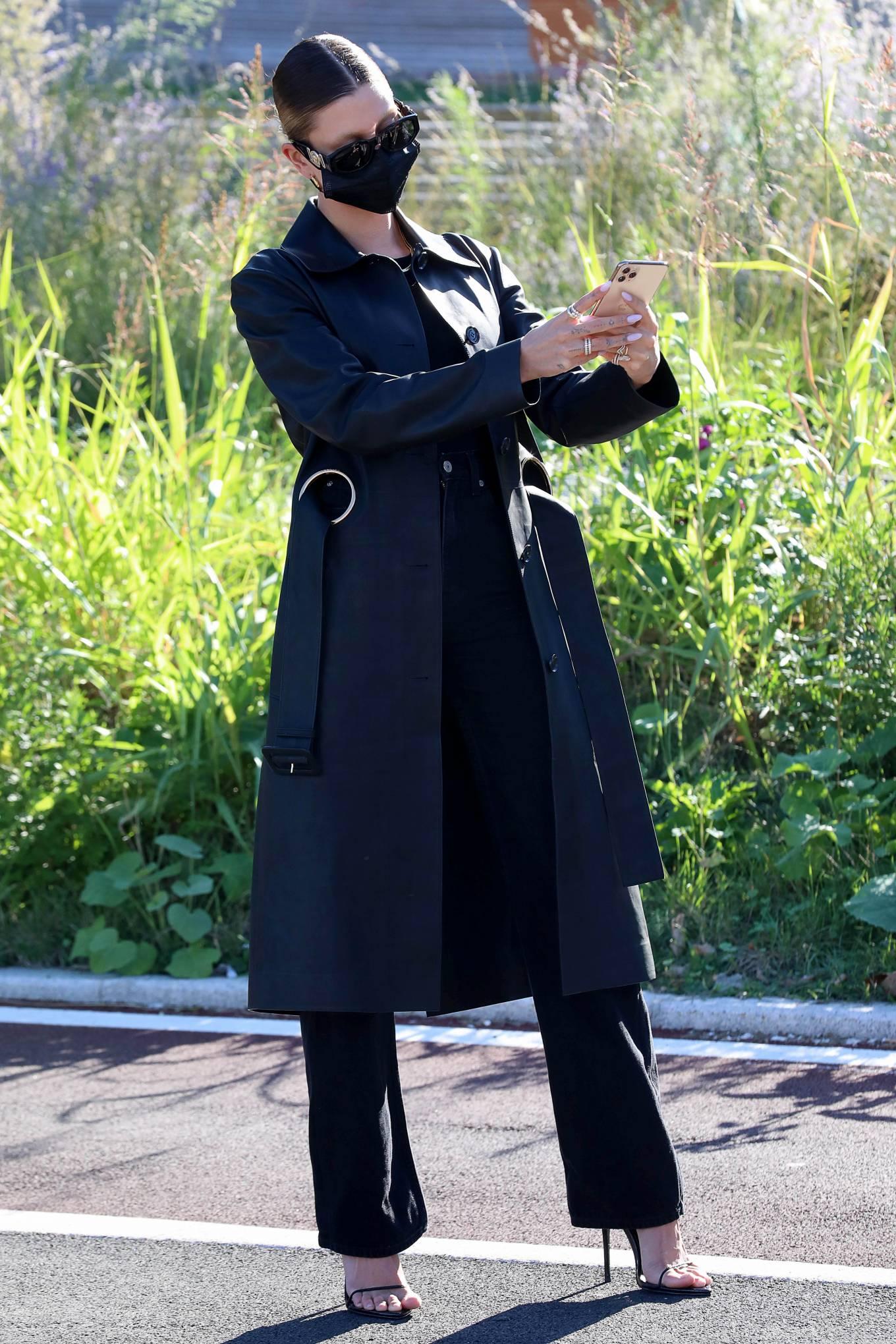Hailey Bieber - Taking pictures in front of her Versace billboard in Milan