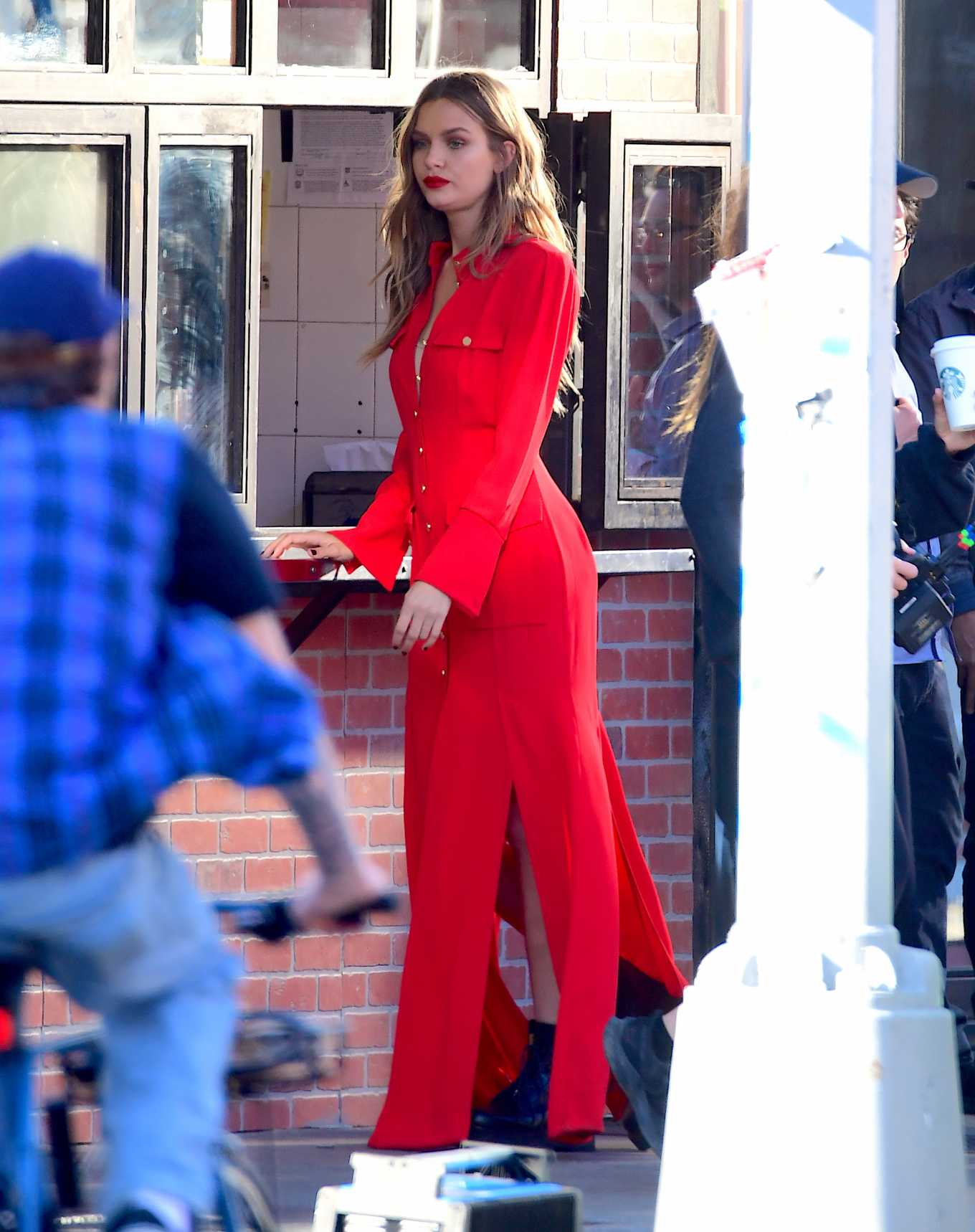 Josephine Skriver in red outfit filming set for Maybelline shoot in NYC