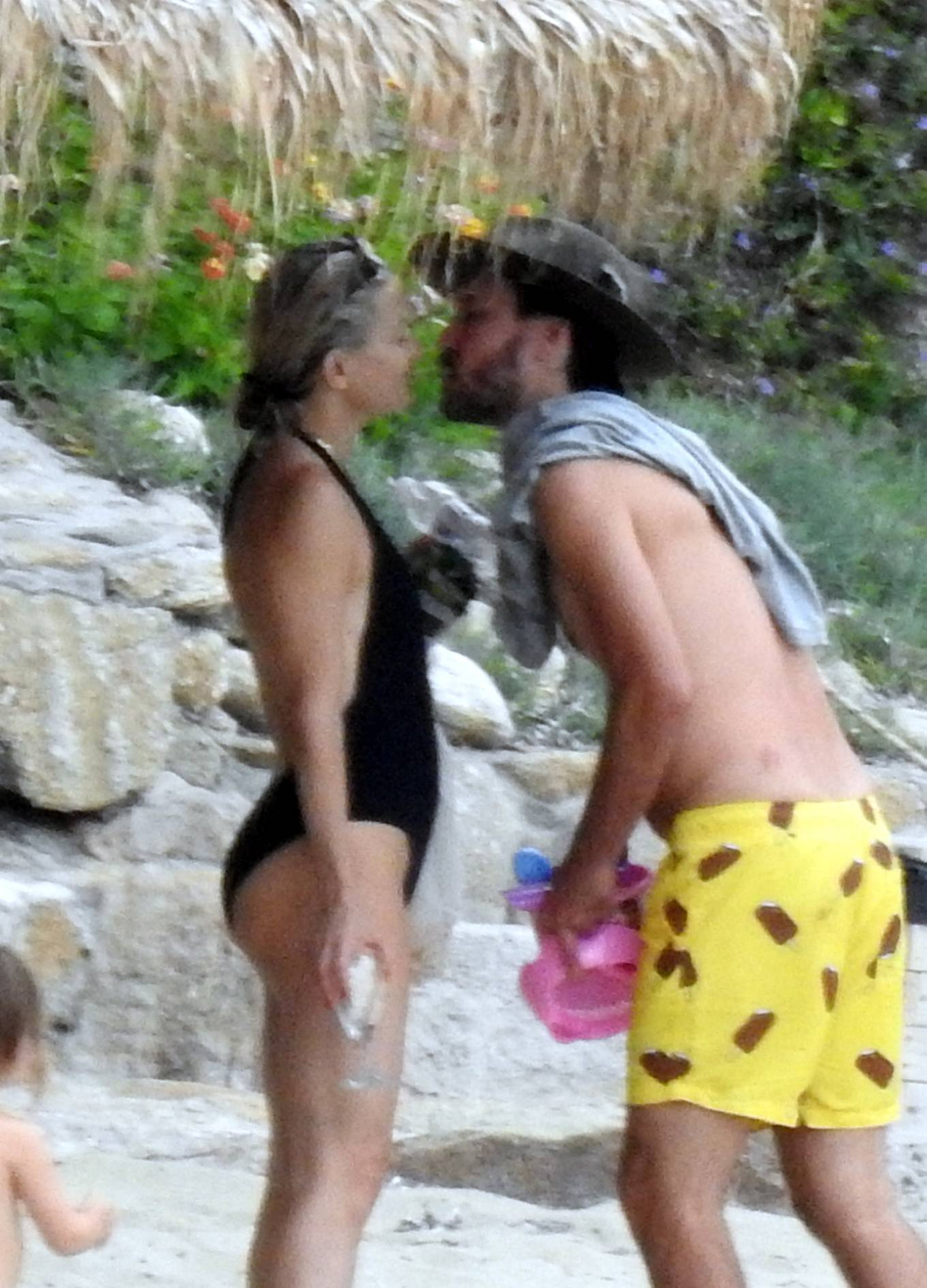Kate Hudson - In a plunging black halter one-piece swimsuit on the beach in Greece