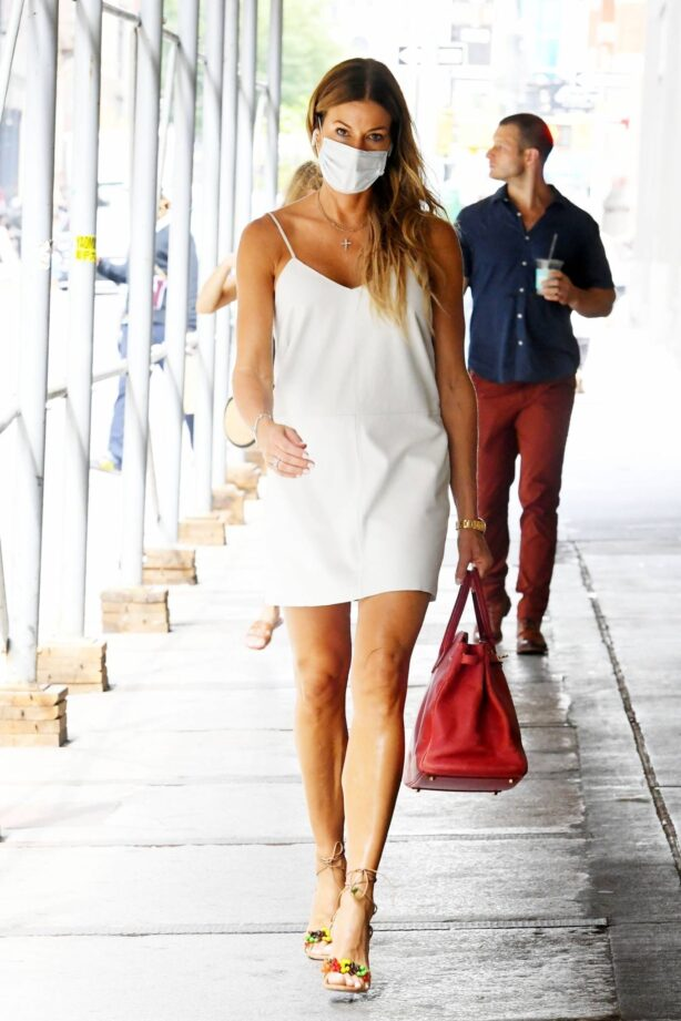 Kelly Bensimon - In white summer dress flashes a peace sign while out in SoHo