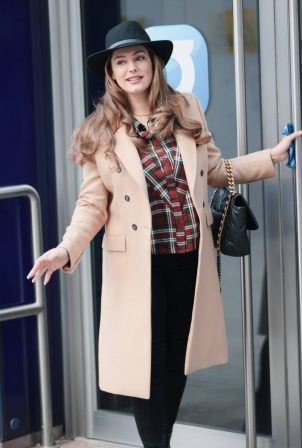 Kelly Brook - In tight denim and beige coat with a fedora hat in London