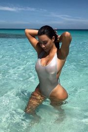 Kim Kardashian posing in a silver one-piece swimsuit on the beach