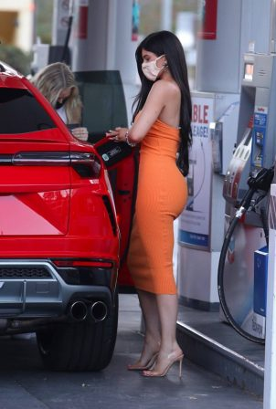 Kylie Jenner - Pumps gas into her new red Lamborghini SUV in Bel Air