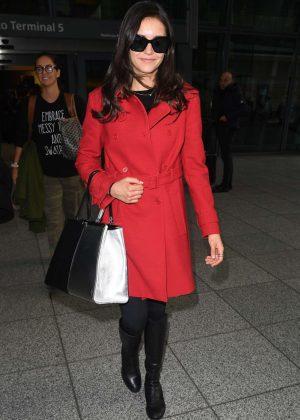 Nina Dobrev in Red Coat at Heathrow Airport in London