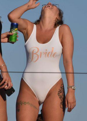 Olivia Buckland in White Swimsuit on boat in Mykonos