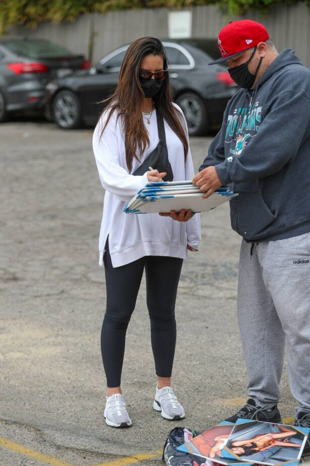 Olivia Munn - signs autographs in West Hollywood