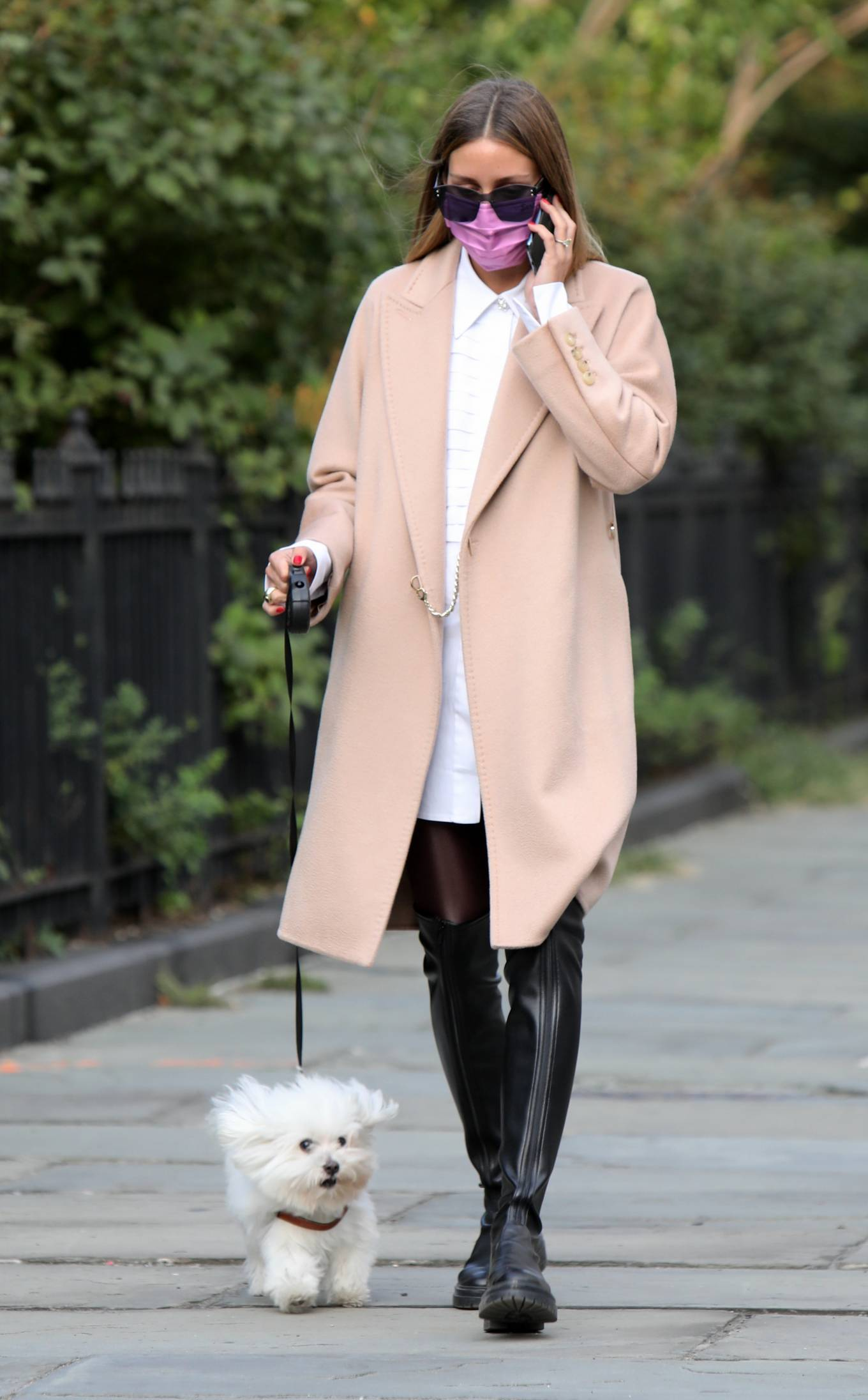 Olivia Palermo - Wearing a white short dress under a coat while out for a walk in Manhattan