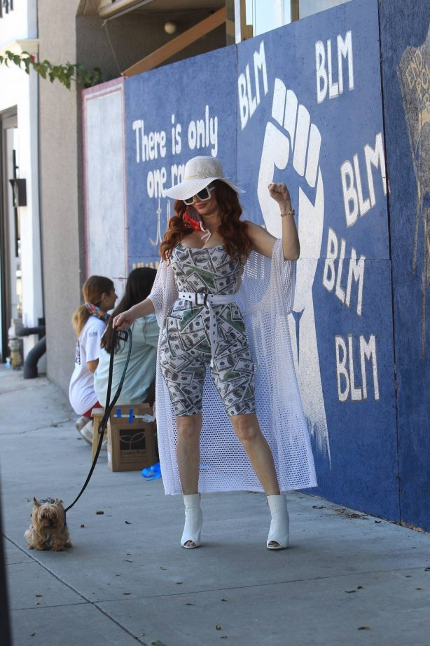 Phoebe Price - Poses next to a BLM mural showing support for George Floyd in Los Angeles
