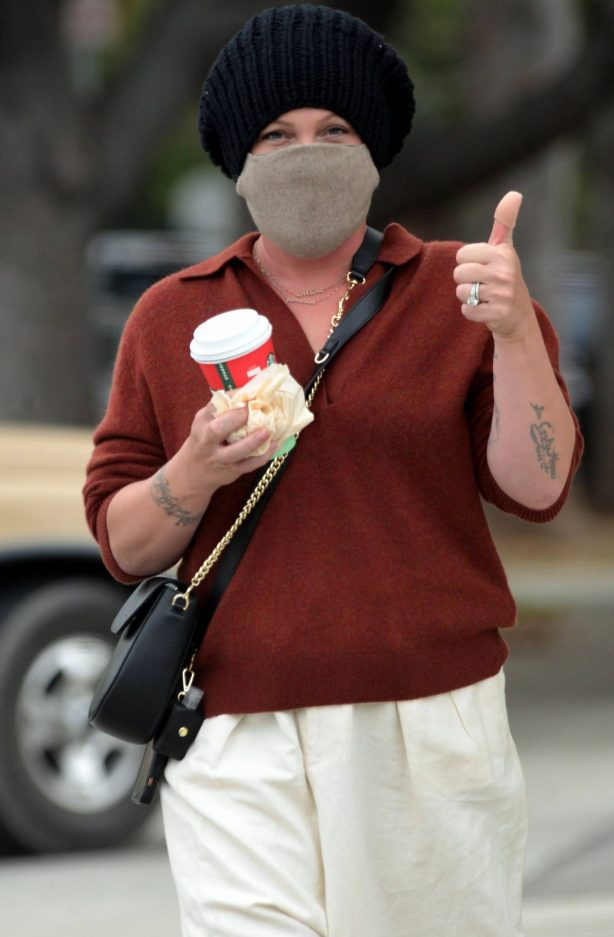Pink - Gives a thumbs at a plastic surgery center in Santa Monica