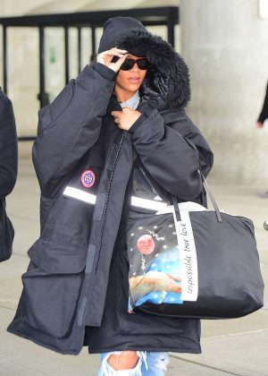 Rihanna in heavy black coat arrives in NYC