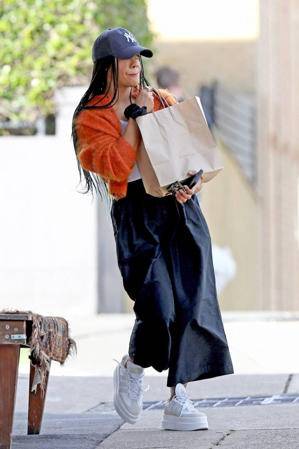 Tessa Thompson - Seen wearing an orange Cardigan and New York Cap with platform trainers