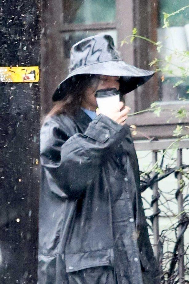 Vanessa Hudgens in a long black coat and a hat in Los Feliz